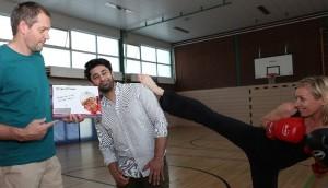 Übungsleiterin Andrea Weiden demonstriert einen Kick über Schulterhöhe von Zahnarzt Mahmoud Zadeh. Links Jörg Benner (DJK Wiking) mit der Zahnrettungsbox. Foto: DJK Wiking
